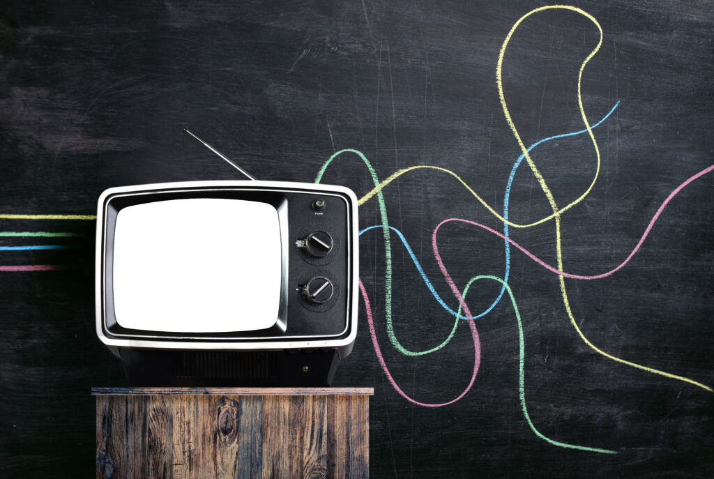 Vintage tv in front of a blackboard. There are multicoloured lines drawn on the chalkboard. The lines are straight up to the tv coming out distorted. Propaganda or disinformation concept